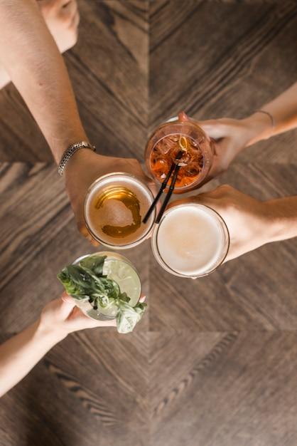 Vista aerea delle mani di amici che tostano bevande Foto Gratuite