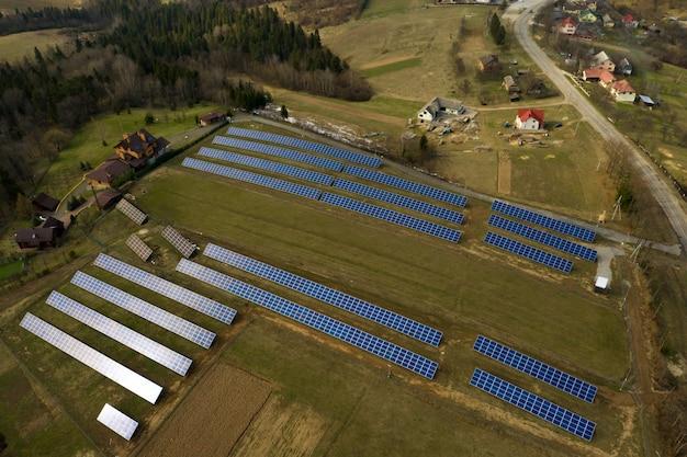 Vista aerea di grande campo del sistema fotovoltaico solare dei pannelli fotovoltaici che producono energia pulita rinnovabile sul fondo dell'erba verde. Foto Premium