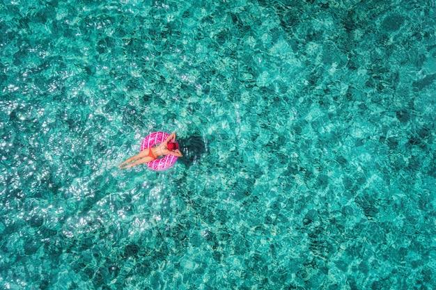 Vista aerea di nuoto esile della giovane donna sull'anello di nuotata della ciambella nel mare blu trasparente al giorno luminoso Foto Premium