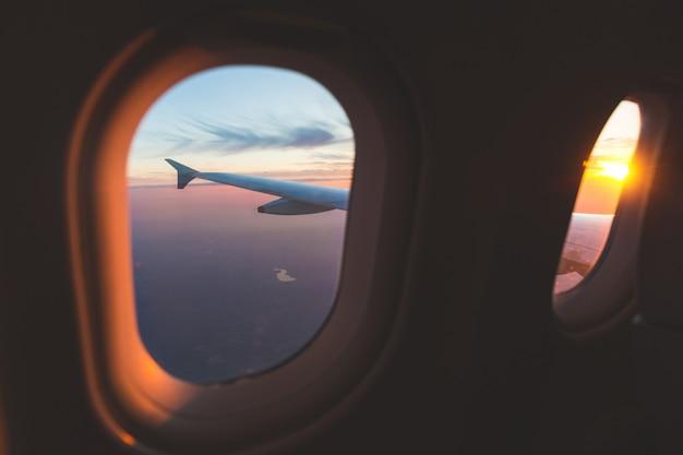 Vista aerea di tramonto attraverso la finestra dell'aeroplano sopra le ali Foto Premium