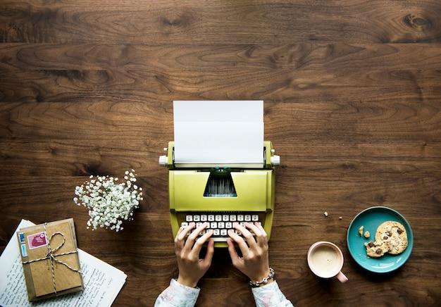 Vista aerea di una donna che scrive su una carta in bianco della retro macchina da scrivere Foto Gratuite