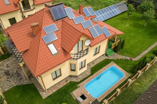 Vista aerea di una nuova casa autonoma con pannelli solari e termosifoni sul tetto e cortile verde con piscina blu. Foto Premium