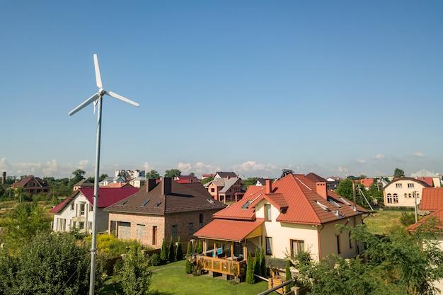 Vista aerea di una nuova casa autonoma con pannelli solari, radiatori di riscaldamento dell'acqua sul tetto e turbina eolica sul cortile verde. Foto Premium