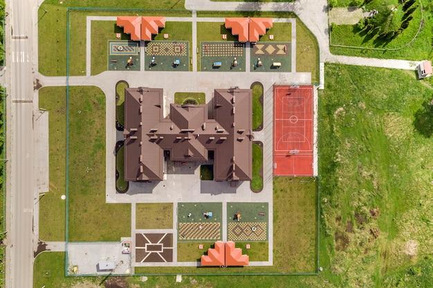 Vista aerea superiore del nuovo edificio prescolare e cortile con nicchie e prati verdi. Foto Premium
