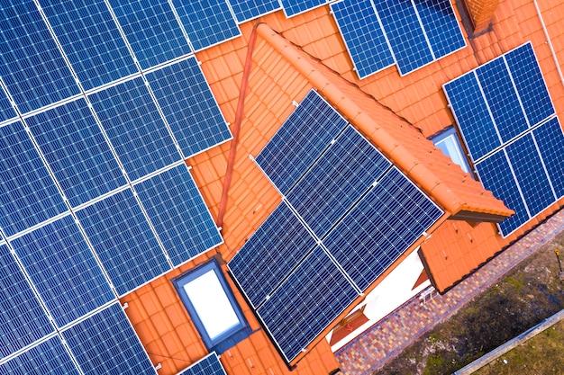 Vista aerea superiore del nuovo moderno cottage casa residenziale con sistema fotovoltaico solare lucido blu pannelli fotovoltaici sul tetto. concetto di produzione di energia verde ecologica rinnovabile. Foto Premium