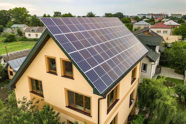 Vista aerea superiore del nuovo moderno cottage casa residenziale con sistema fotovoltaico solare lucido blu pannelli fotovoltaici sul tetto Foto Premium