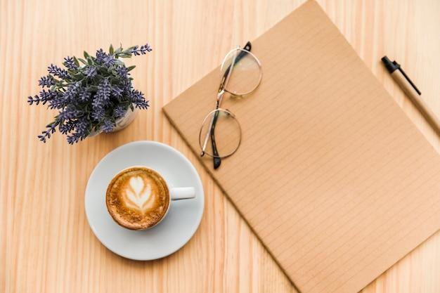 Vista ambientale del latte del caffè, delle cancellerie e del fiore della lavanda su fondo di legno Foto Gratuite