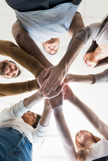 Vista bassa comunità di persone che tengono le mani Foto Gratuite