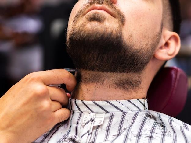 Vista bassa del cliente che ottiene il taglio della barba Foto Gratuite