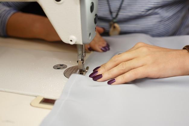 Vista da sopra sulle mani del sarto femminile che lavora alla macchina per cucire. vestire industria manifatturiera Foto Premium