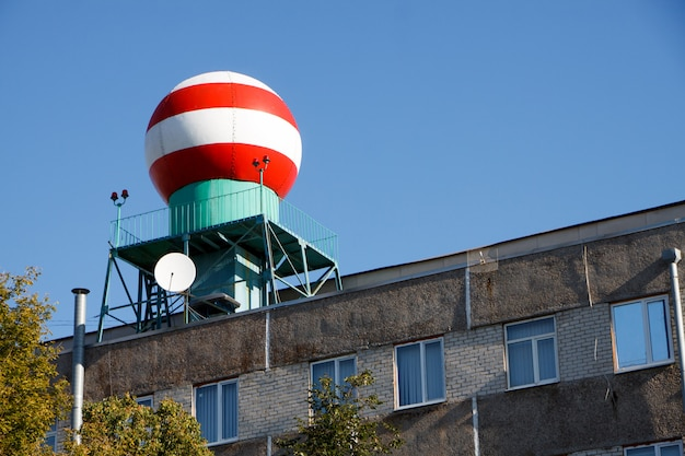 Vista dal basso della sfera rosso-bianca sulla costruzione del servizio meteorologico contro il cielo blu Foto Premium