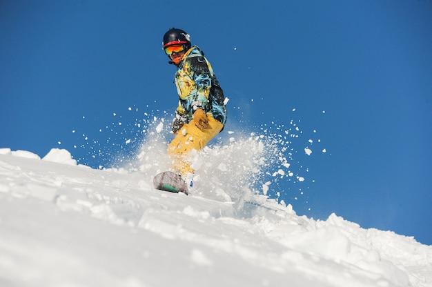 Vista dal basso dello snowboarder freeride che scivola giù per il pendio Foto Premium