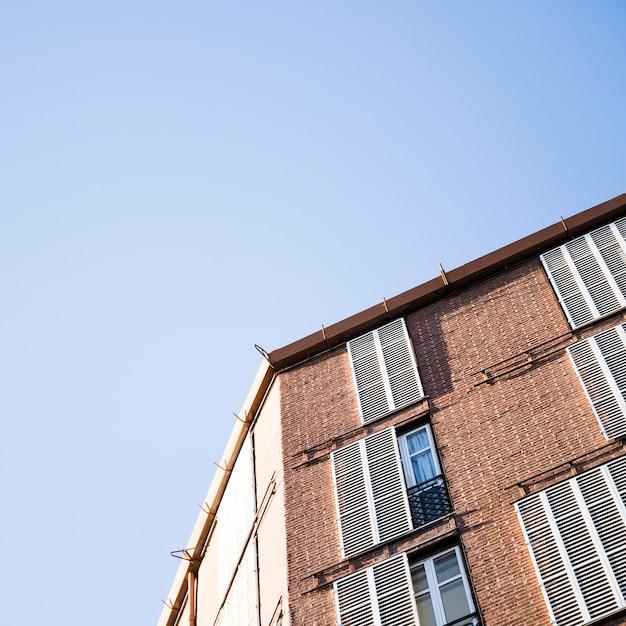 Vista dal basso di un edificio con finestre contro il cielo blu Foto Gratuite