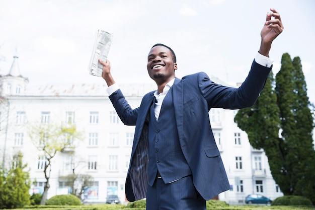 Vista dal basso di un giovane imprenditore spensierato tenendo il giornale alzando le mani Foto Gratuite
