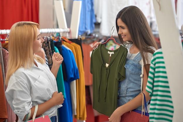 Vista dal lato di due amici che scelgono i vestiti in negozio Foto Premium