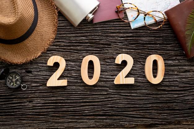 Vista dall'alto 2020 numero di felice anno nuovo sul tavolo di legno con oggetto accessorio avventura Foto Premium