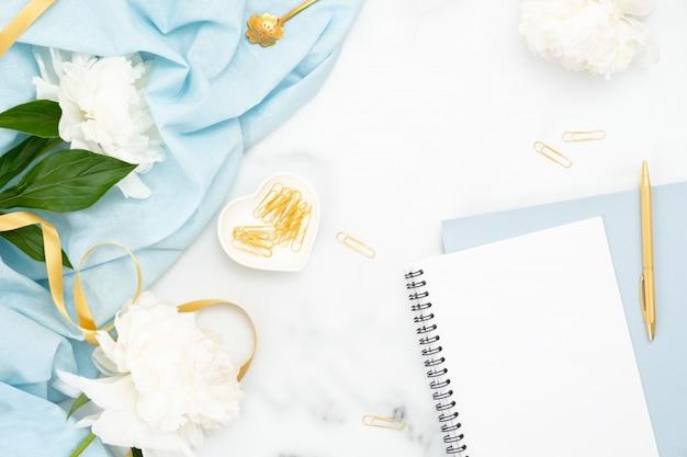 Vista dall'alto accessori femminili dorati, blocco note di carta, fiori di peonia Foto Premium