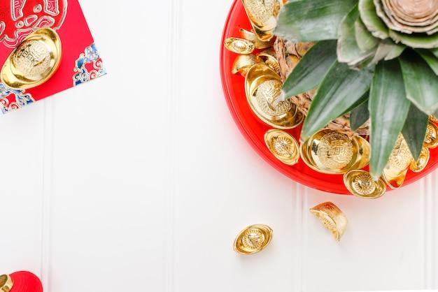 Vista dall'alto ananas con gruppo di lingotti d'oro nel vassoio rosso sul tavolo di legno bianco Foto Premium