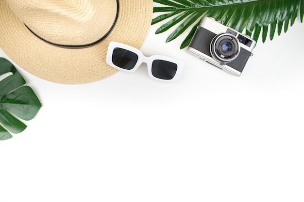 Vista dall'alto, attrezzatura turistica con cappelli di paglia, macchine da presa, occhiali da sole e fogliame estivo su uno sfondo bianco. oggetto estivo. viaggio . Foto Premium