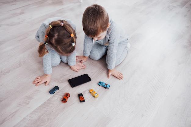 Vista dall'alto. bambini che usano gadget digitali a casa. fratello e sorella in pigiama guardano i cartoni animati e giocano sul loro tablet tecnologico Foto Gratuite