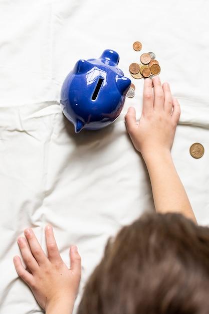 Vista dall'alto bambino contando i suoi soldi dal salvadanaio Foto Gratuite