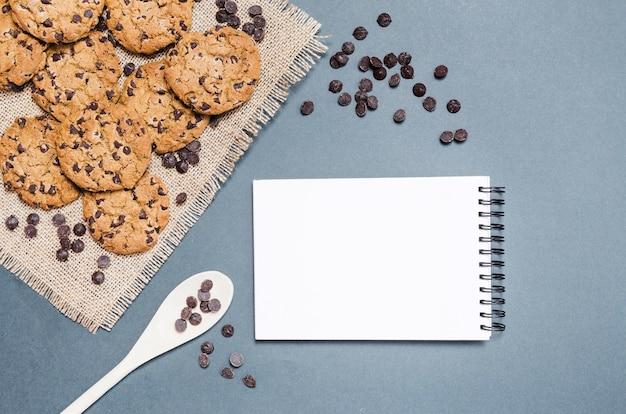 Vista dall'alto biscotti con gocce di cioccolato e notebook Foto Gratuite