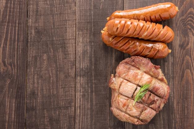 Vista dall'alto bistecca alla griglia e salsiccia su uno sfondo di legno Foto Premium