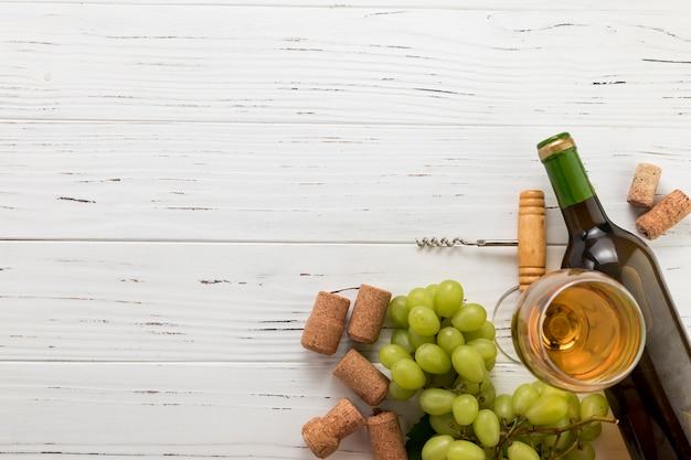 Vista dall'alto bottiglia di vino con vetro e grappolo d'uva Foto Gratuite