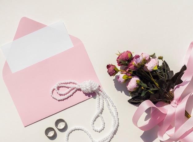 Vista dall'alto busta rosa con invito a nozze accanto al mazzo di rose Foto Gratuite