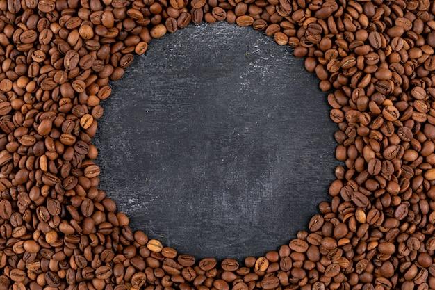 Vista dall'alto chicchi di caffè sulla superficie scura Foto Gratuite