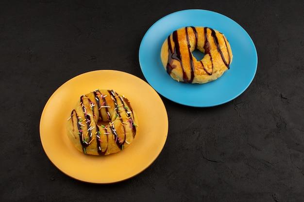 Vista dall'alto ciambelle al cioccolato all'interno di piatti colorati al buio Foto Gratuite
