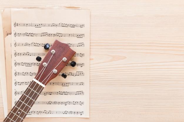 Vista dall'alto collo di chitarra con spartito musicale Foto Gratuite