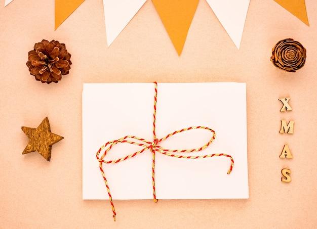 Vista dall'alto composizione di natale con regalo, carta bianca vuota, pigne, bandiere Foto Premium