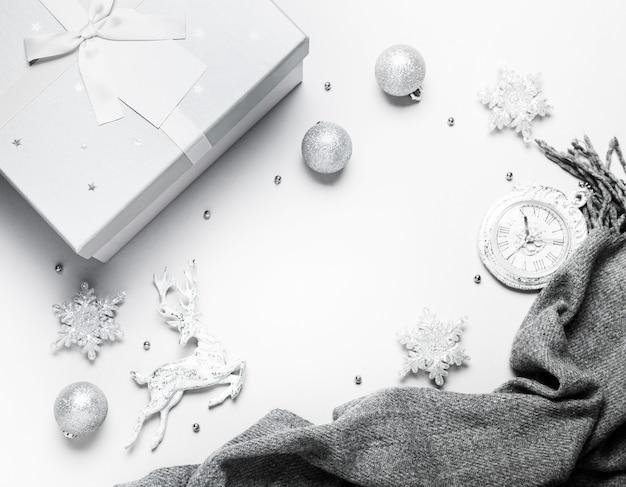 Vista dall'alto composizione di natale o capodanno su uno sfondo grigio e bianco con decorazioni natalizie bianche e argento, cervi, fiocchi di neve, palline e orologio Foto Premium