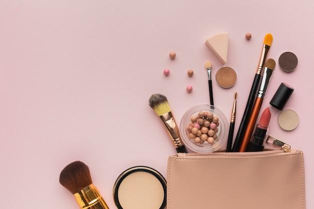 Vista dall'alto con prodotti per il trucco con beauty-case Foto Gratuite