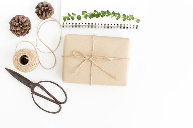 Vista dall'alto confezione regalo e accessori su bianco, confezione regalo fatta a mano sul pavimento bianco Foto Premium