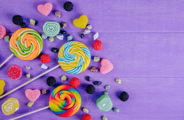 Vista dall'alto copia spazio ghiaccioli colorati con marmellata colorata di varie forme e pietre di cioccolato su uno sfondo viola Foto Gratuite