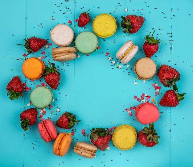 Vista dall'alto copia spazio macarons multicolori con fragole su sfondo blu Foto Gratuite