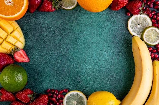 Vista dall'alto copia spazio mix di frutti mango banana fragole arancione limone con cornice su uno sfondo verde Foto Gratuite