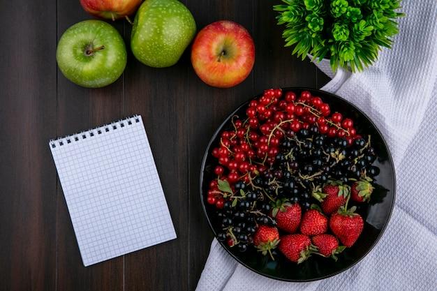 Vista dall'alto copia spazio ribes rosso e nero con fragole su un piatto con mele e un quaderno su uno sfondo di legno Foto Gratuite