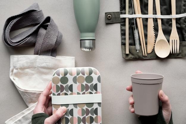 Vista dall'alto creativa, concetto di pranzo al sacco zero rifiuti, scatola da pranzo da asporto con posate in bambù, scatola riutilizzabile, sacchetto di cotone e mano con tazza da caffè. vita ecologica, disteso su carta artigianale. Foto Premium