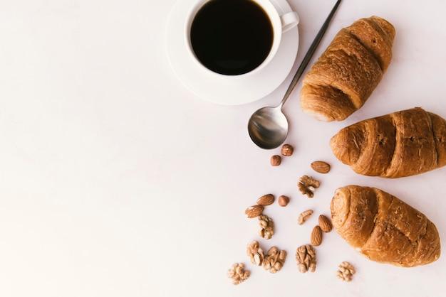 Vista dall'alto croissant e caffè con spazio di copia Foto Gratuite