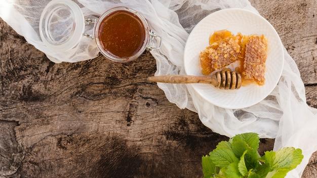 Vista dall'alto cucchiaio di miele con pezzi a nido d'ape Foto Gratuite