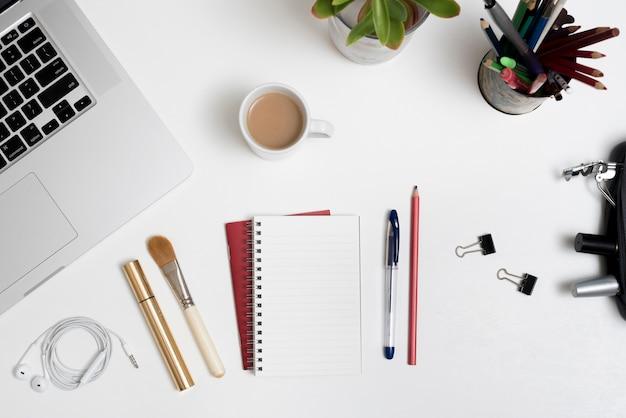 Vista dall'alto dei prodotti cosmetici; cancelleria per ufficio; tazza di caffè e portatile con pianta sulla scrivania Foto Gratuite