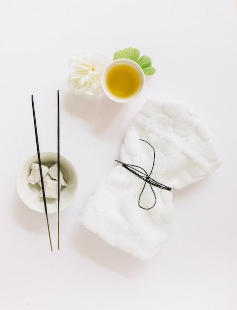 Vista dall'alto del bastone di incenso; pietra pomice; fiore; foglia di gingko; olio e tovagliolo legato su sfondo bianco Foto Gratuite