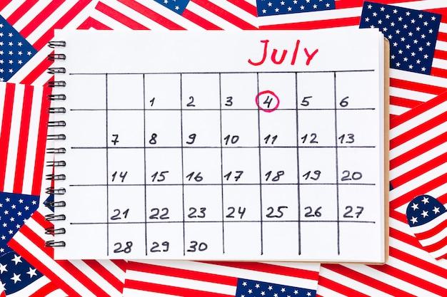 Vista dall'alto del calendario per il mese di luglio con bandiere americane Foto Gratuite