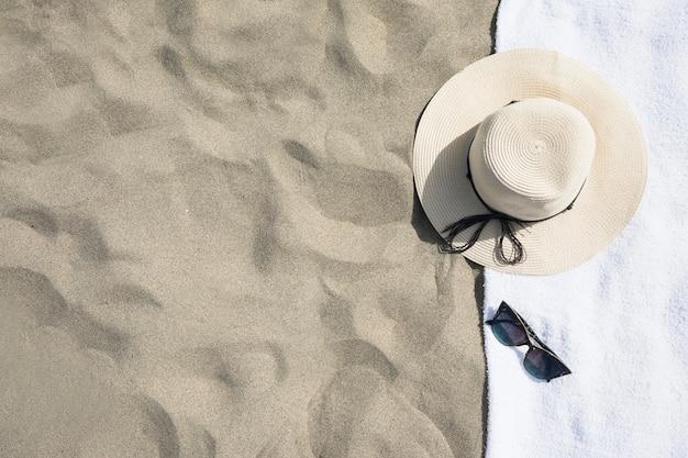 Vista dall'alto del cappello sul telo da mare Foto Gratuite