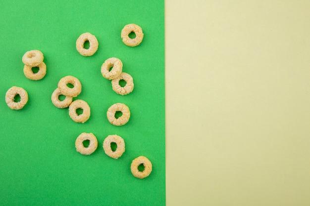 Vista dall'alto del ciclo e cereali sani su superficie verde e sfondo giallo Foto Gratuite