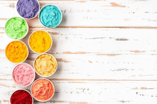 Vista dall'alto del colorato gelato arcobaleno in tazze. copia spazio Foto Premium