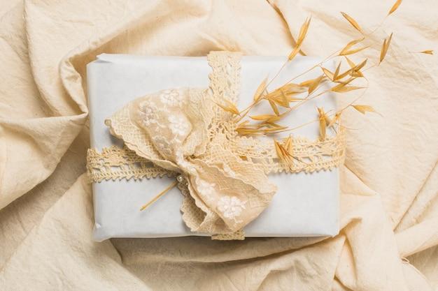 Vista dall'alto del contenitore di regalo decorato su tessuto rugoso Foto Gratuite